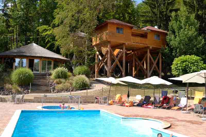 Das Baumhotel Styrassicpark in der Steiermark gehört zu den familienfreundlichsten Baumhaushotels in Österreich (Ansicht Baumhaus mit Pool)