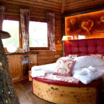 Baumhaushotels in Österreich: Schlafzimmer mit dekoriertem Bett im Baumhaus Prechtlhof