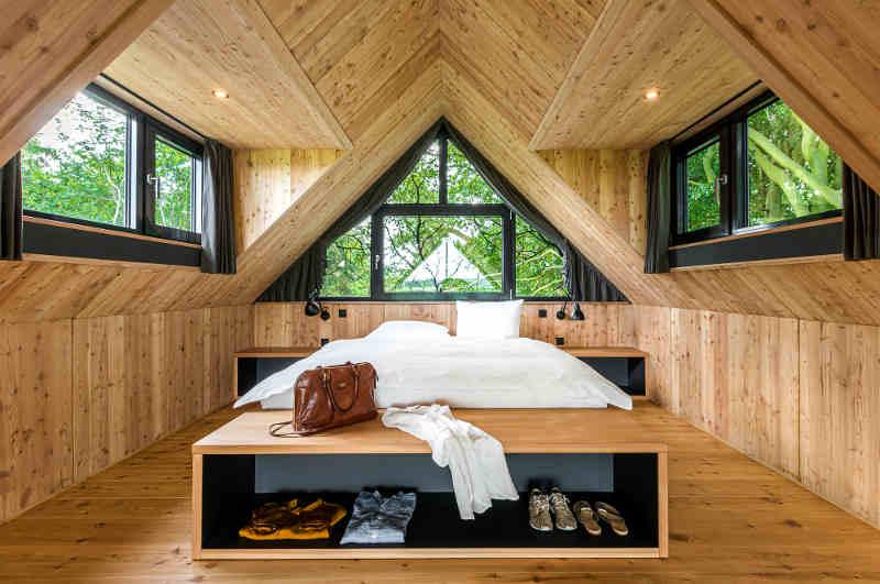 Blick in den großzügigen Schlafbereich der Lütetsburg Lodges in Ostfriesland. deren modernes Design typisch für viele Baumhaushotels in Niedersachsen ist.