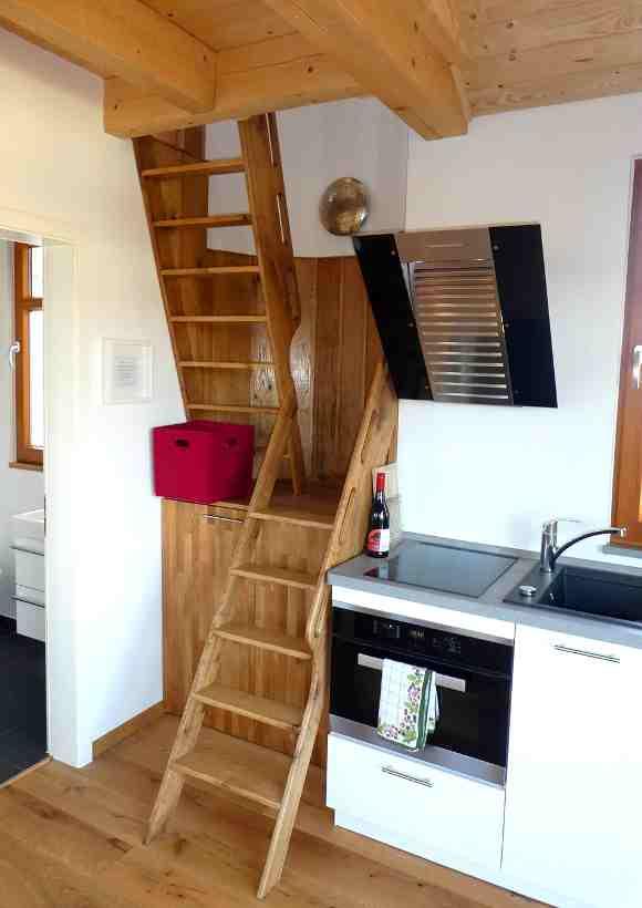 Küche mit Treppenaufgang im niedersächsischen Baumhaus Wesertal können bis zu vier Personen übernachten.