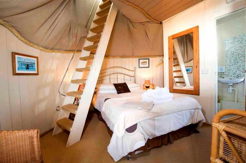 Schlafzimmer mit Leitertreppe im alten Leuchtturm von Dale in Pembrokeshire (Wales)